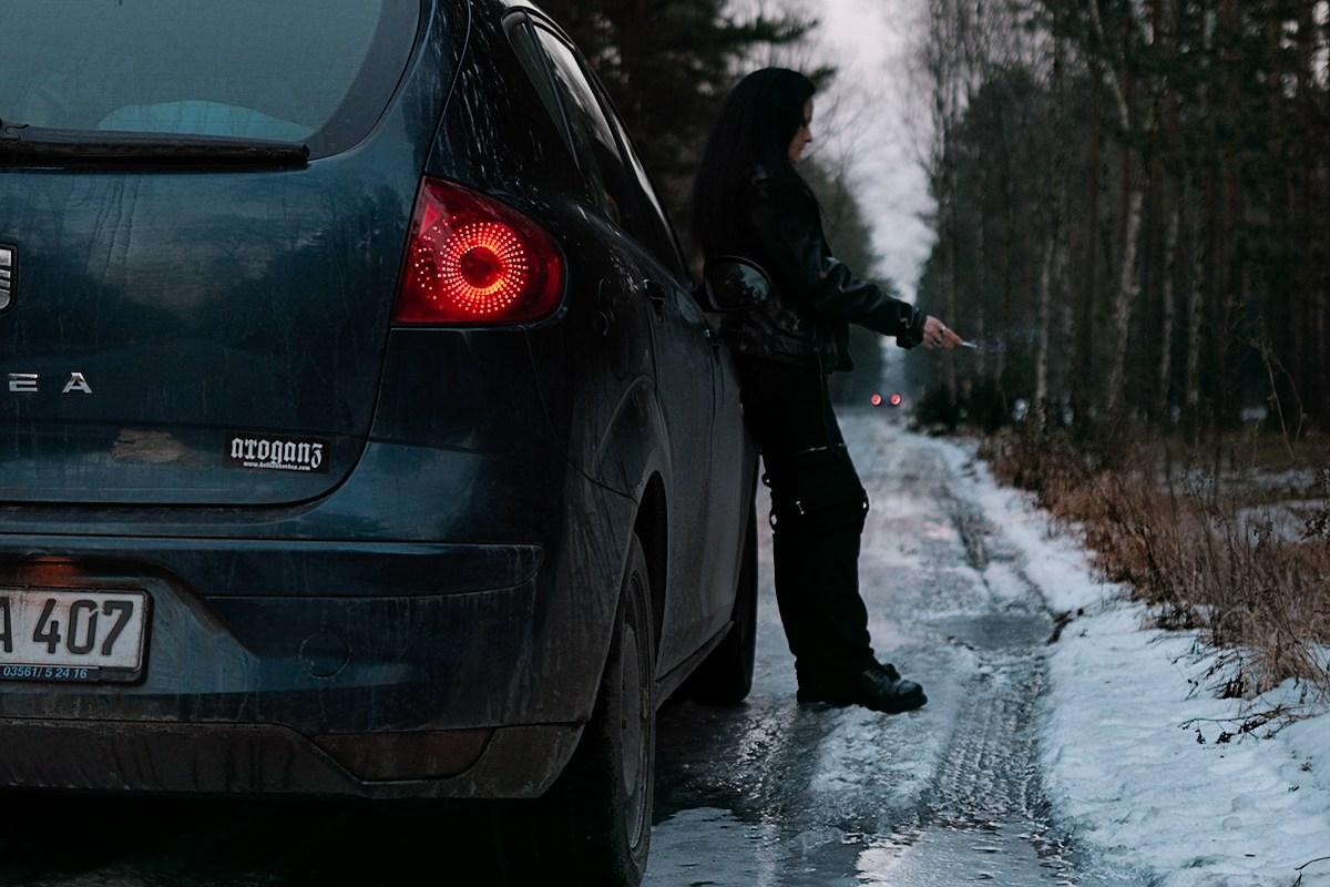eine frau in lederjacke lehnt an einem auto und raucht eine zigarette auf einem waldweg, der gefroren ist