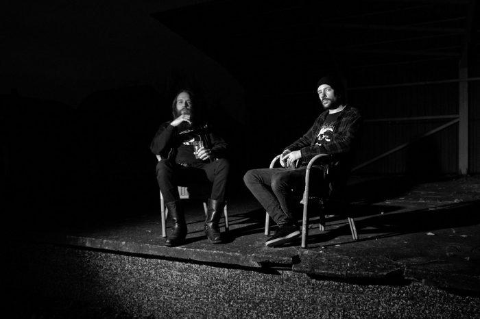 zwei Männer sitzen in Korbstühlen und blicken in die Kamera