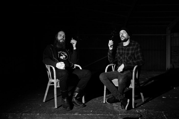 zwei Männer sitzen in Korbstühlen, rauchen und blicken in die Kamera