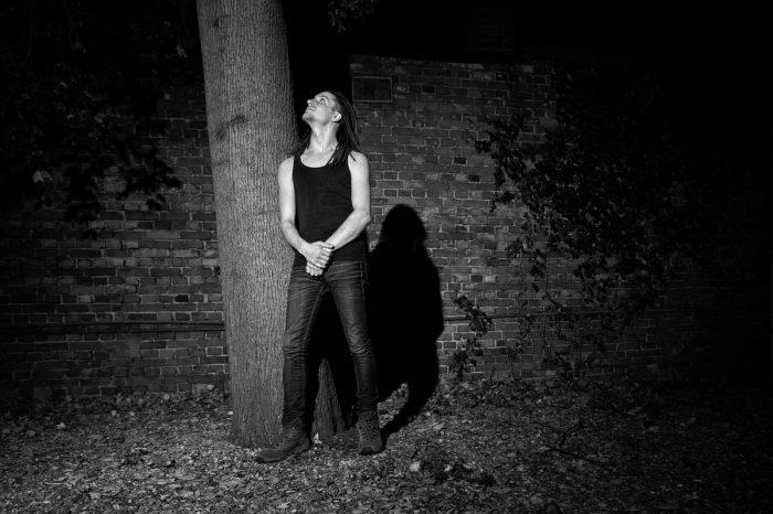 ein Mann steht an einem Baum und sieht an ihm nach oben