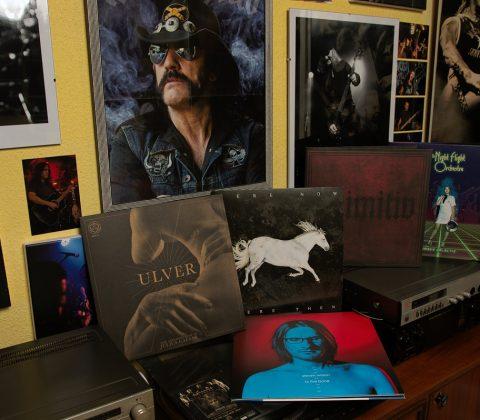 fünf Vinyl-Schallplatten auf einer Anrichte mit Fotos von Musikern im Hintergrund