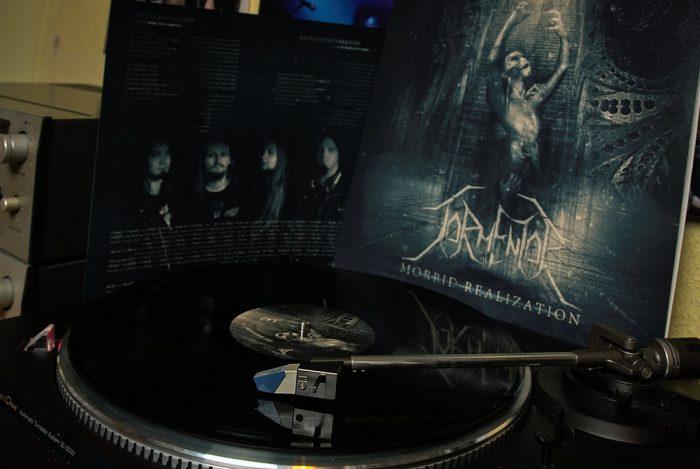 """Tormentor """"Morbid Realization"""" Schallplatte beim Abspielen, Cover im Hintergrund"""" Schallplatte beim Abspielen, Cover im Hintergrund"""