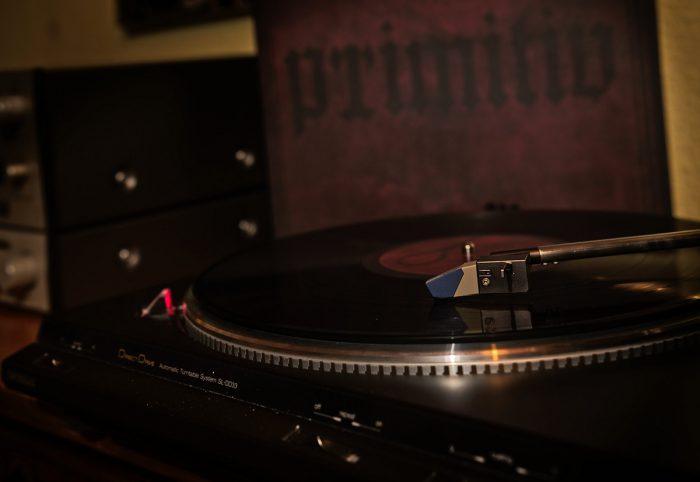 """Arroganz """"Primitiv"""" Schallplatte beim Abspielen, Cover im Hintergrund"""