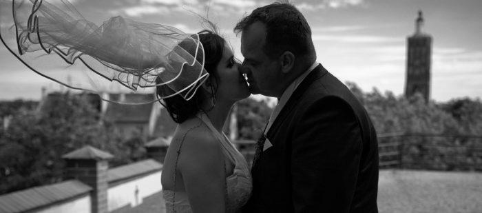 schwarz weiß Fotografie eines Hochzeitspaares auf einer Anhöhe mit wehendem Schleier im Wind und einer Kirche im Hintergrund