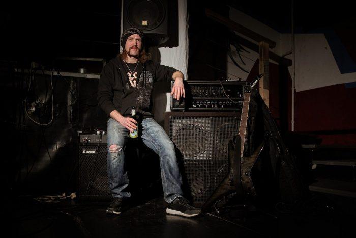ein Mann mit Mütze und Bier in der Hand sitzt lässig auf einem Gitarrenverstärker