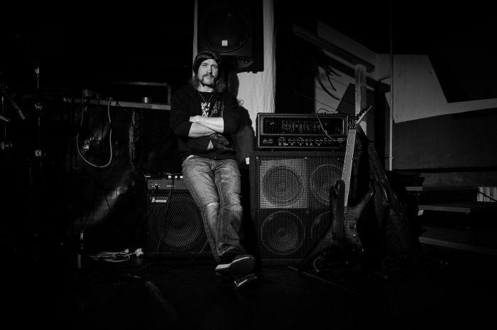 ein Mann mit Mütze sitzt lässig auf einem Gitarrenverstärker