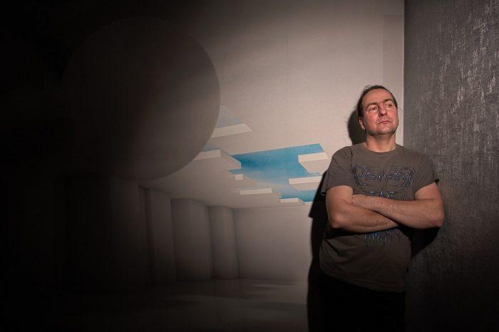 Ein Mann steht mit verschränkten Armen in einer Zimmerecke und schaut nach rechts
