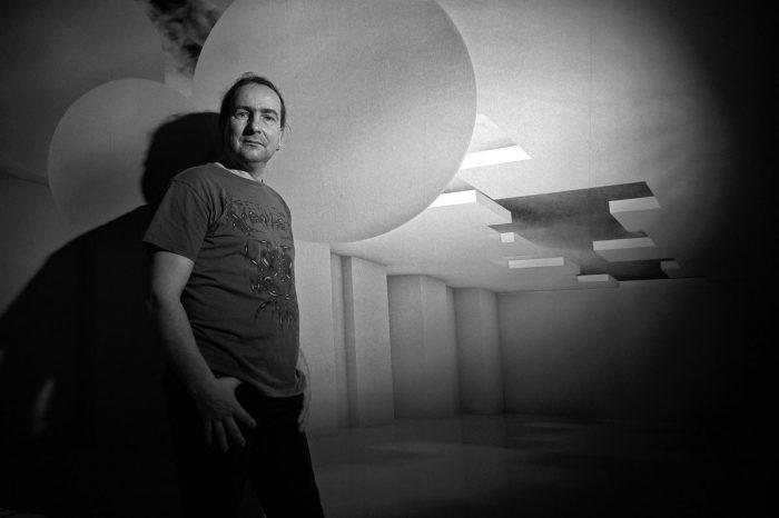 Ein Mann steht mit Daumen in den Hosentaschen an eine Wand gelehnt und schaut in die Kamera