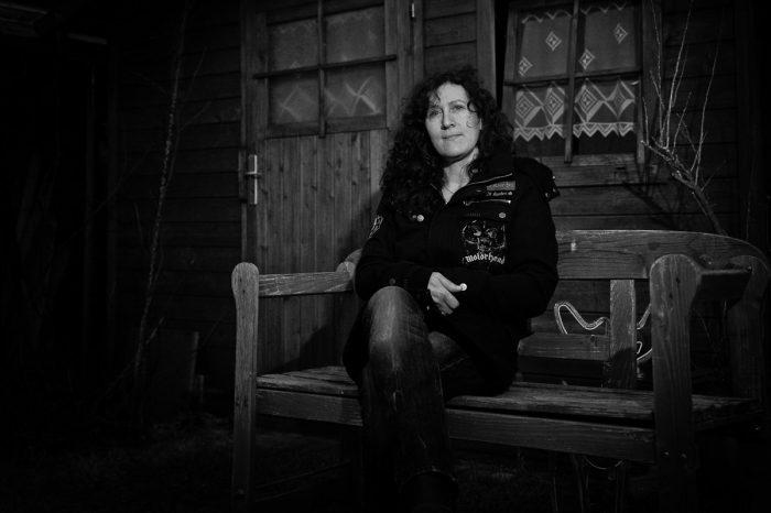 eine Frau sitzt vor einer Holzhütte auf einer Band und blickt in die Kamera