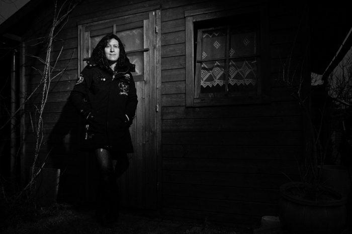 eine Frau steht vor einer Holzhütte und blickt in die Kamera