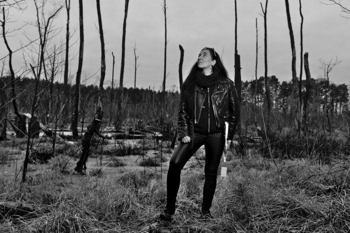 eine Frau steht in an einem morastigem Waldesrand