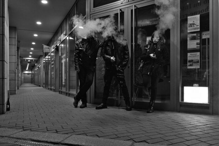 Zwei Männer und eine Frau stehen nachts in einer Ladenpassage und rauchen