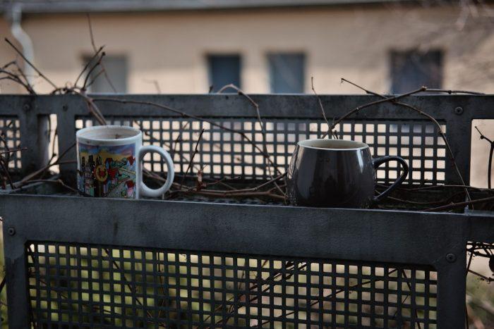 zwei Kaffeetassen stehen in einem leeren blumenkasten auf einem balkon