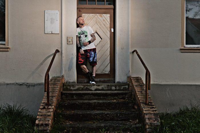 ein mann mit bier in der hand, steht an einer haustür auf dem treppenabsatz