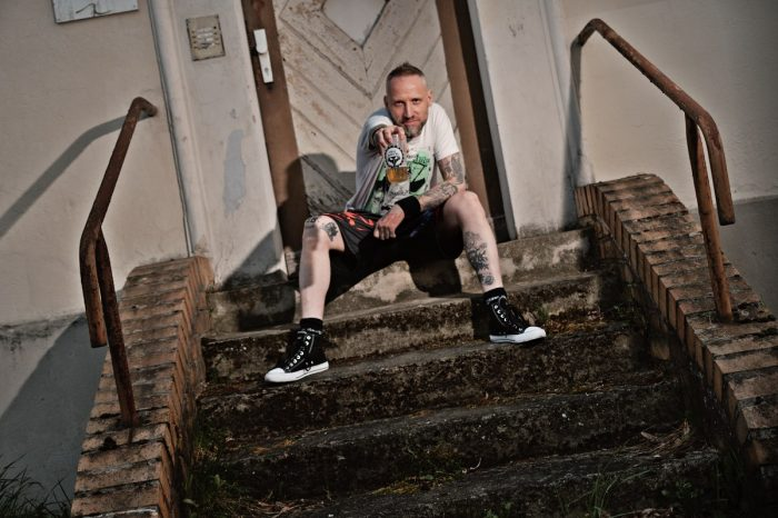 ein mann sitzt auf einem treppenabsatz und hält ein bier in die Kamera