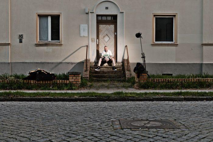 straßenszene - ein mann wird vor einem Haus auf einem treppenabsatz sitzend, fotografiert