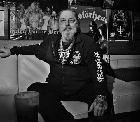 ein mann sitzt auf einem hellem ledersofa, raucht und schaut dabei in die Kamera