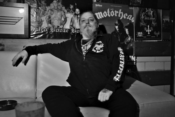 ein mann sitzt auf einem hellem ledersofa, und schaut in die kamera