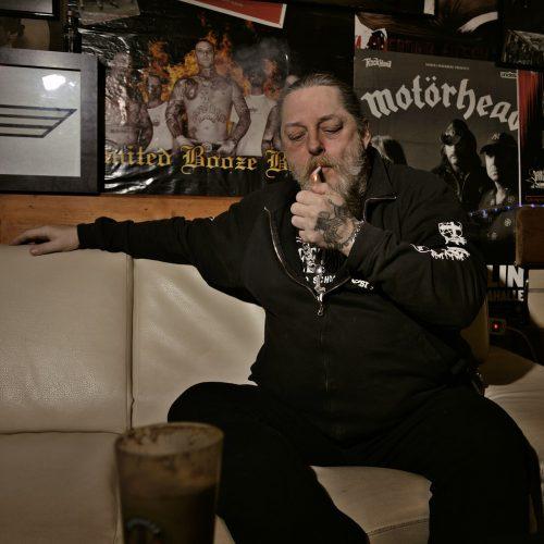 ein mann sitzt auf einem hellem ledersofa, und steckt sich eine zigarett an