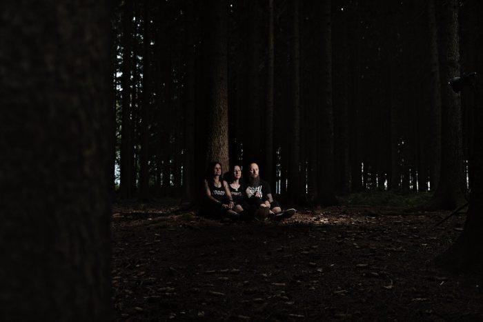 drei menschen sitzen in einem dunklen wald