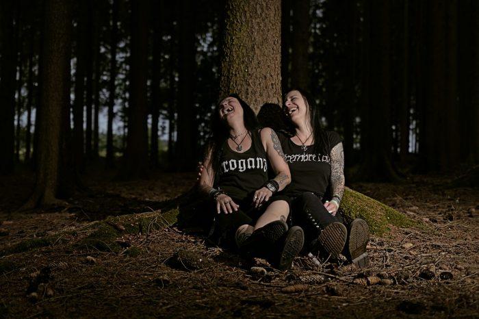 zwei frauen sitzen vor einem baum und lachen herzhaft