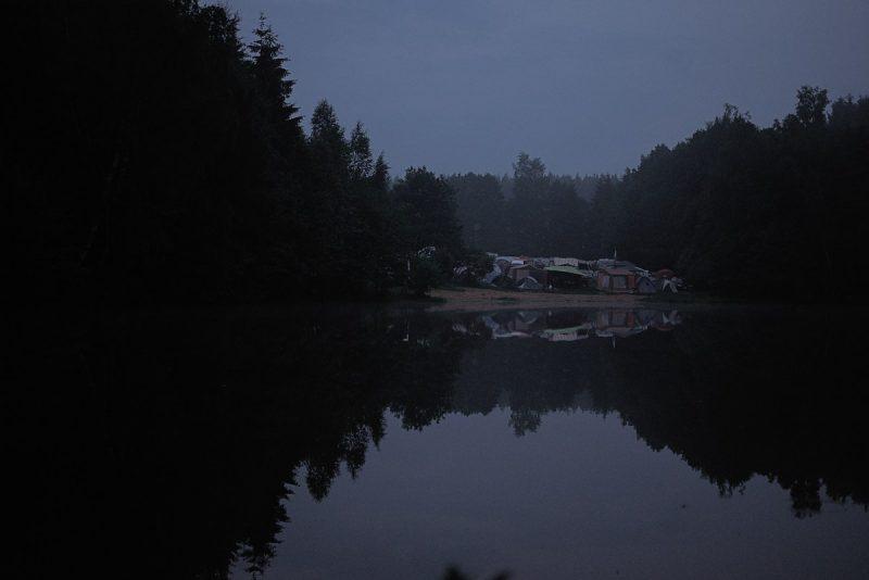 abendliche stimmung an einem kleinem see mit blick auf einen campingplatz zur blauen stunde