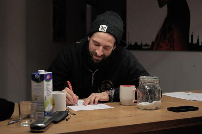 ein mann sitzt am tisch und schreibt auf einen zettel