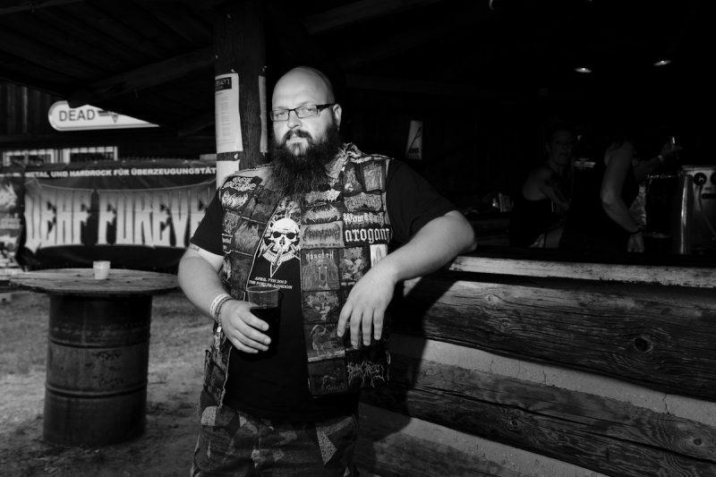 ein heavy metal fan mit kutte steht an einer bar und hält seinen cuba liebre und schaut in die Kamera