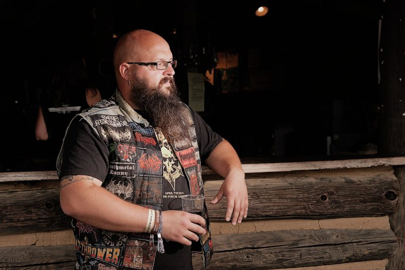 ein heavy metal fan mit kutte steht an einer bar und trinkt cuba liebre