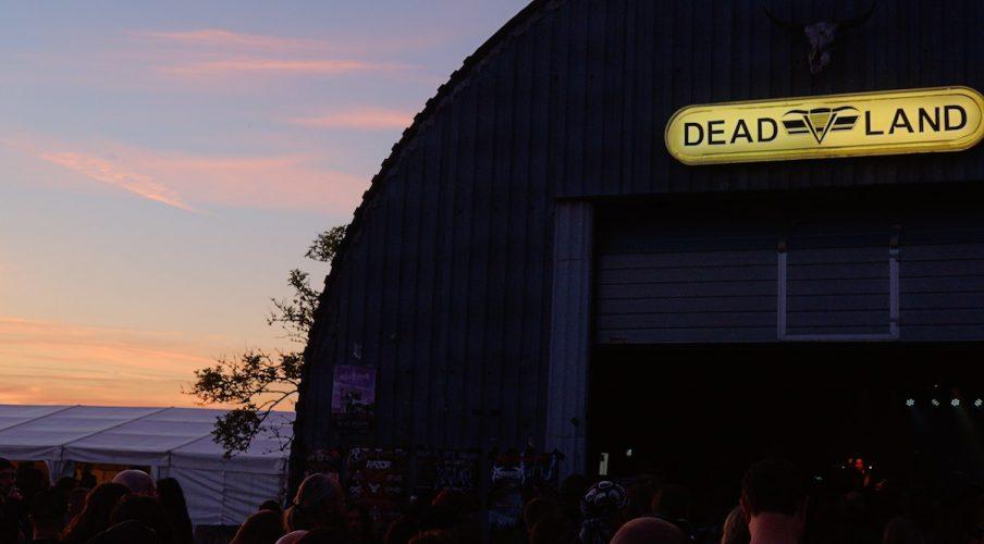 """ein flugzeughanger mit der aufschrift """"dead land"""" im sonnenuntergangslicht"""