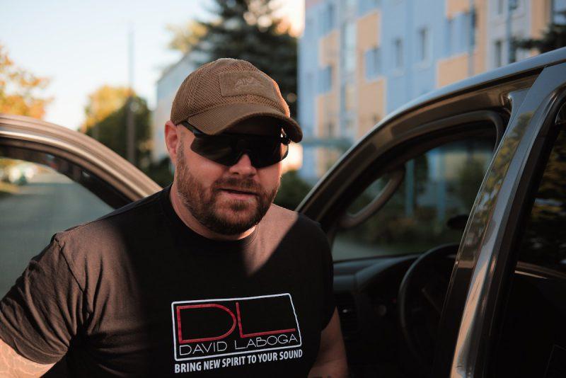 ein mann mit sonnenbrille und baseballcape steht in der geöffneten tür eines autos und schaut in die kamera
