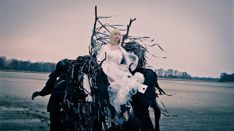"""filmszene aus """"artfremd"""": die hauptdarstellerin auf einer art thron, welcher von schwarzen monstern getragen wird"""