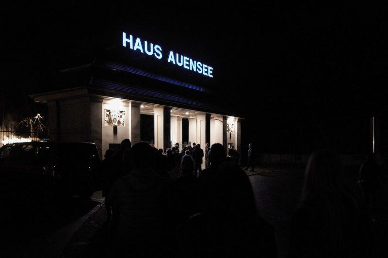 eingangsbereich am haus auensee bei nacht, ein blauer schriftzug über dem portal