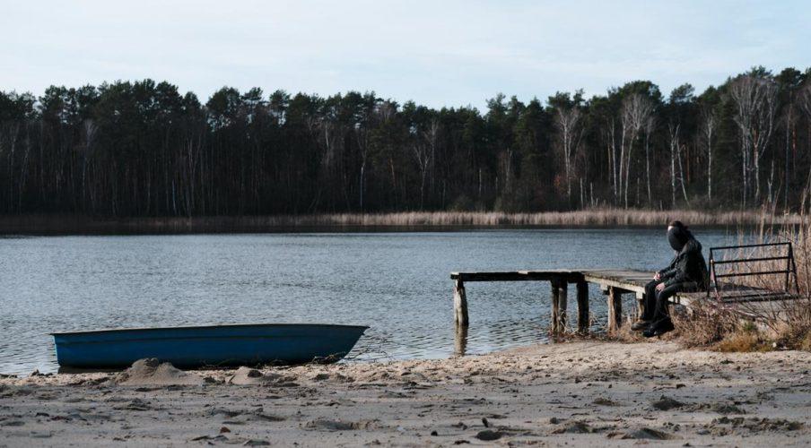 ein boot liegt ruhig am strand und auf dem steeg sitzen zwei menschen