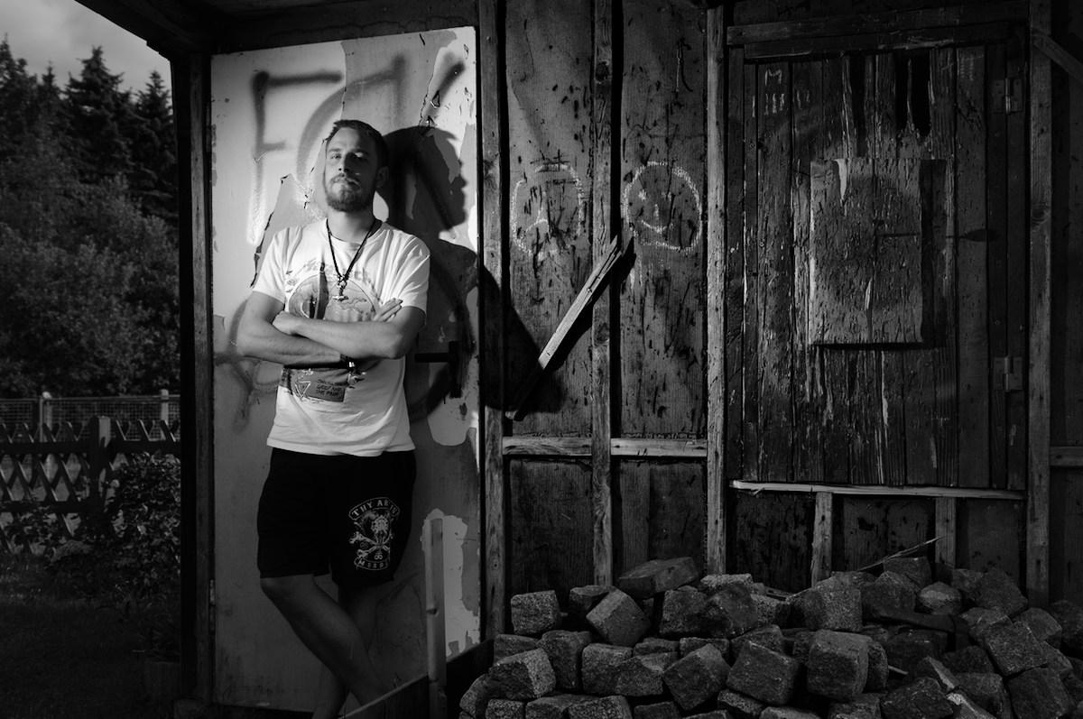 ein junger mann steht mit verschränkten armen vor einer gartenlaube und sieht in die kamera gartenlaube