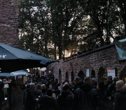 Metal Fans versammeln sich zu einem Festival auf einer Burgruine vor Bierständen
